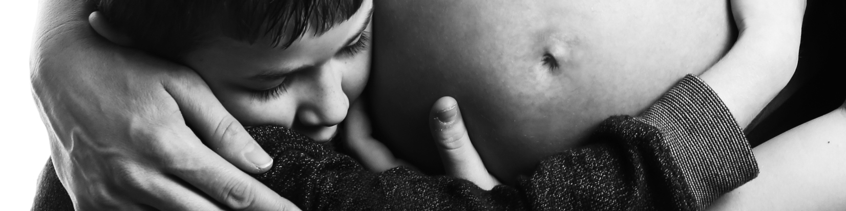 Maternity photograph of a toddler hugging mothers belly